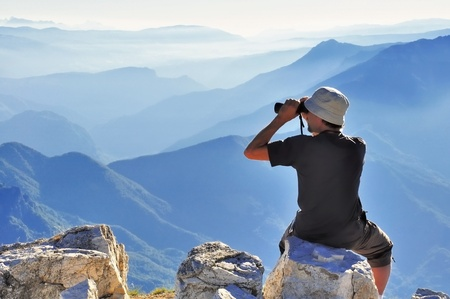 A hiker sitting and watching the horizon Standard-Bild