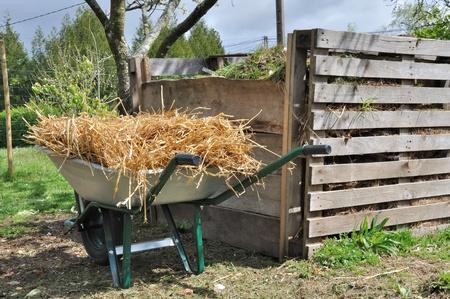 houten compostvat voor organisch afval en kruiwagen vol met stro Stockfoto