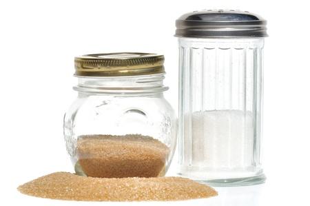 Zuckerdosen braunem Zucker und weiß auf weiß vor einem Haufen brauner Zucker Standard-Bild - 13734633