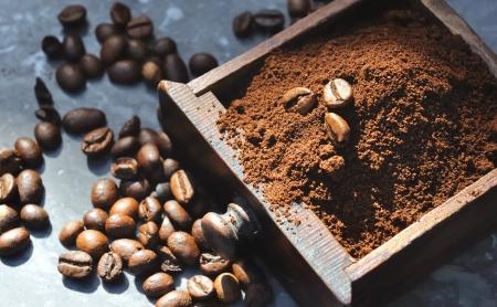 koffiebonen in de gemalen koffie opgevangen in de bak van een molen