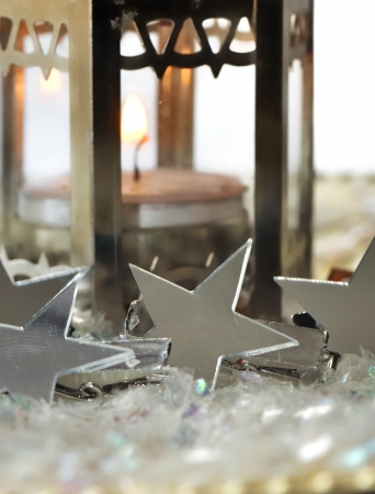 candle holder: silver stars against a lit candle holder