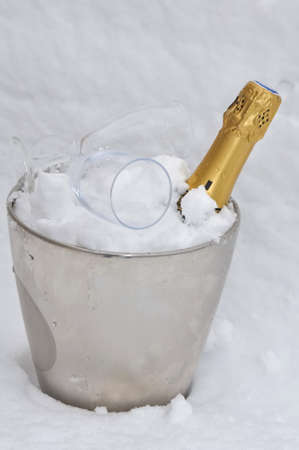 champagne bottle and glasses on a bucket oin the snow  Stock Photo - 16822783