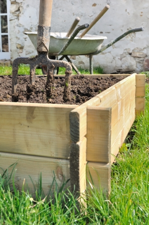 spade in a wooden  planter for vegetable garden photo