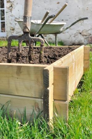 spade in een houten planter voor moestuin