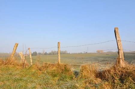 fencing wire: picket fence and barbed wire in a field under a blue sky