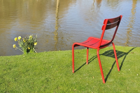 red chair installed on a green lawn in front of a river photo