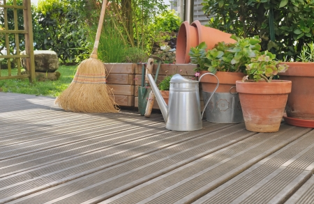 various accessories for gardening and cleaning on a wooden deck
