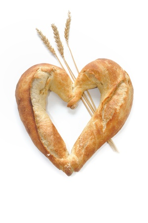 sprigs: bread shaped heart on sprigs of wheat on white background