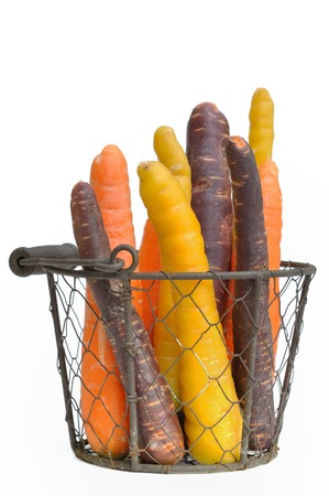 carrots of different colors in a basket on white background