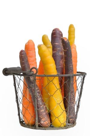 wortelen van verschillende kleuren in een mand op een witte achtergrond Stockfoto