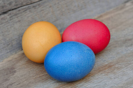 planck: three painted eggs in straw on wooden board Stock Photo