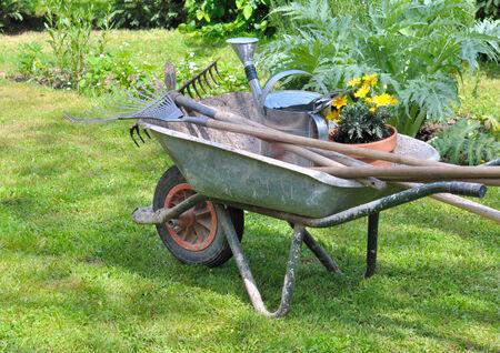 Gartenwerkzeuge in einer Schubkarre mit Topfblumen Standard-Bild - 28076679