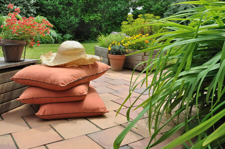 cushions and straw hat on a terrace of a country garden