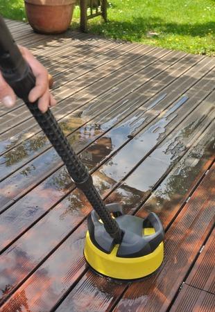 man de hand houden van een wasmachine hoge druk op houten terras