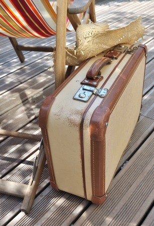 porches: straw hat on small retro suitcase next to a lounge chair on wooden terrace