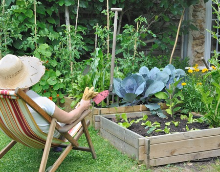 woman in lounge chair contemplating her garden with tools in hand Stock Photo