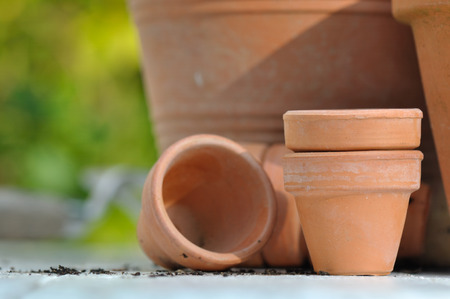 different sizes of terracotta pots on outdoor table Stock Photo