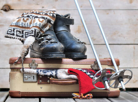 old ski boots on a small  suitcase full of warm clothes Standard-Bild