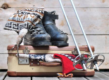 ropa de invierno: botas de esquí de edad en una pequeña maleta llena de ropa de abrigo