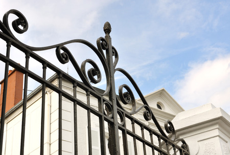 details of a black wrought iron gate in front of house