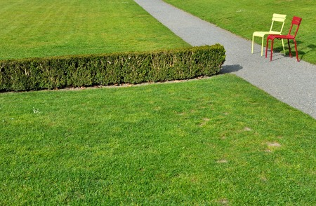 grass plot: chairs in the driveway of a park facing a hedge dividing a grass plot