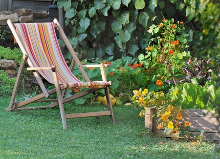 folwer: lounger chair in a garden with folwer and patch Stock Photo
