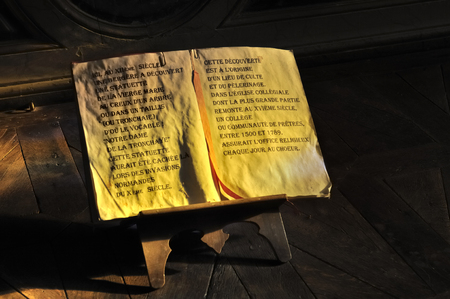 piety: open old manuscript on wooden easel in a church