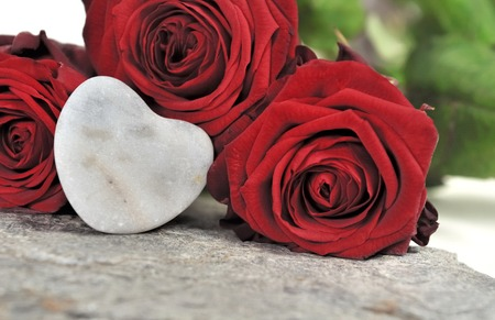 red pebble: heart shaped pebble and red roses Stock Photo