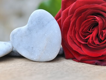 red pebble: close on a heart shaped pebble next to a red rose Stock Photo