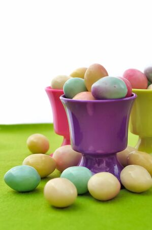 egg cups: egg cups filled with small Easter eggs on green and white background Stock Photo