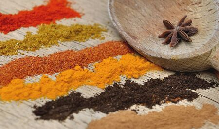 anis: bands of different spices powder and anis in  spoon on wooden  background Stock Photo