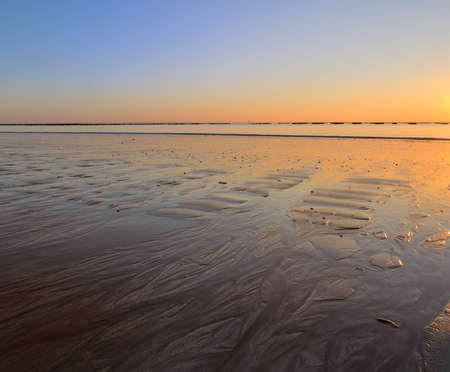 vendee: sunset on wet sand at low tide witht