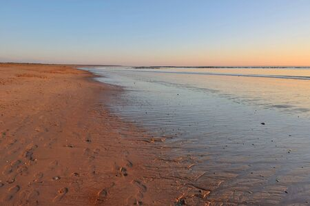 vendee: sunset on wet sand at low tide with footsprint