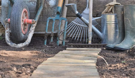 wood agricultural: rustic gardening tools on the soil with a wooden path