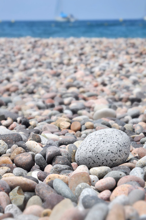 whote: whote pebbles i a beach with bleu sea in background