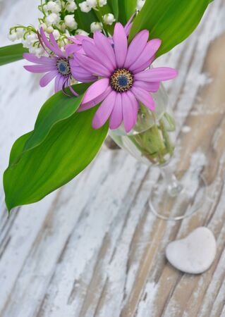 planck: bouquet of spring flowers on a wooden planck with a little heart Stock Photo