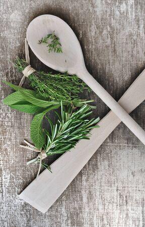 aromatický: aromatické byliny na dřevěném pozadí s lžícemi