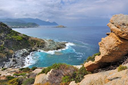 rough sea: wild coast of Cap Corse with rough sea under  cloudy sky