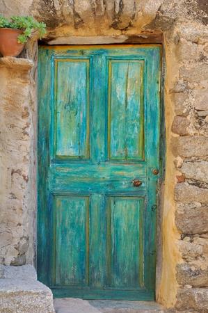 emerald stone: old wooden door painted in emerald green stone facade Stock Photo
