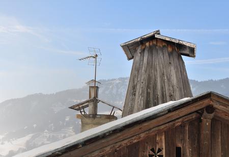 flue: wooden chimney flue on roof of cottage typical Savoyard Stock Photo