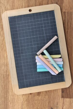 chalks: slate with chalks on wooden background