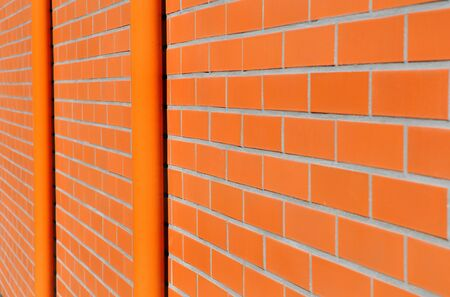 tile cladding: orange tile on a building facade with discharge pipe