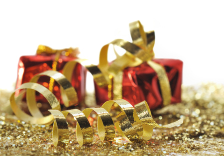 red glittery: golden curling ribbon in front of gifts on white background