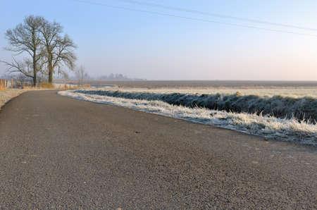 asphalt paving: country road asphalt paving in winter crossin frost field