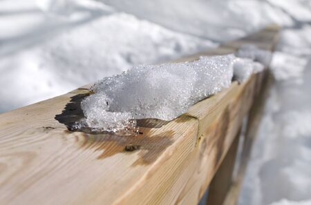 guard rail: close on pile of snow on a wooden railing
