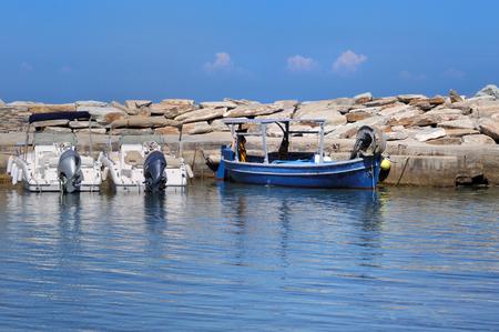 seawall: blue boat moored to a seawall on blue sea