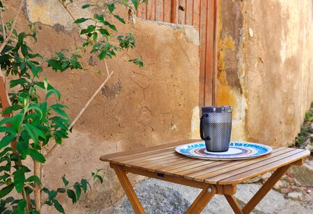 cup on a wooden table in a courtyard on background ocher facade