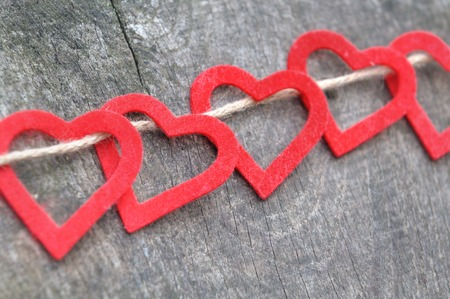 passed out: red hearts cut out of felt and passed to a rope on wood background