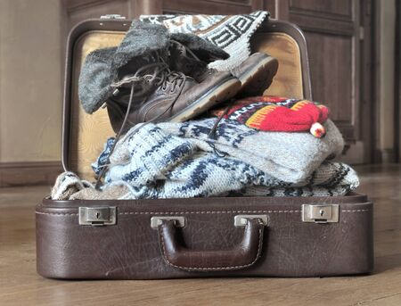 open suitcase: open suitcase full of warm clothes on the floor