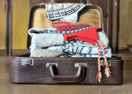 warm clothes: open suitcase full of warm clothes on the floor